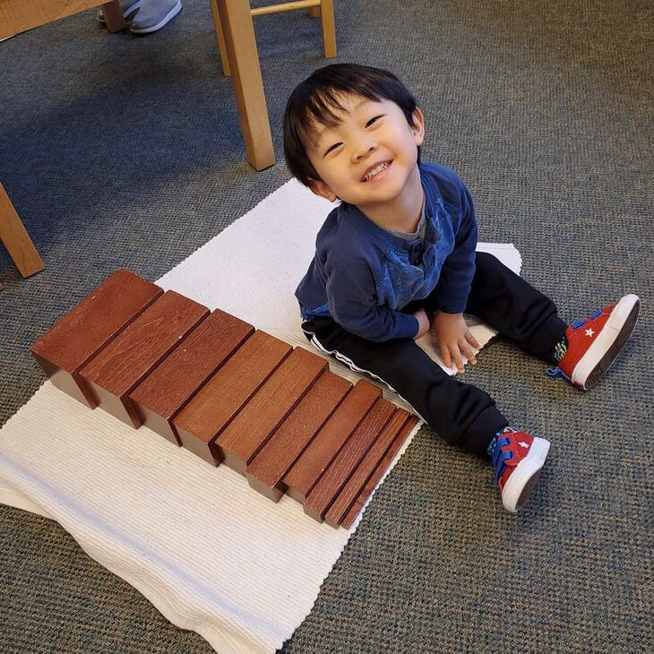 Child organizing wooden blocks from smallest to largest.